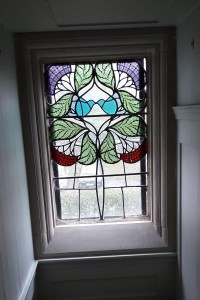 The use of the rowan motif in the stained glass throughout the house